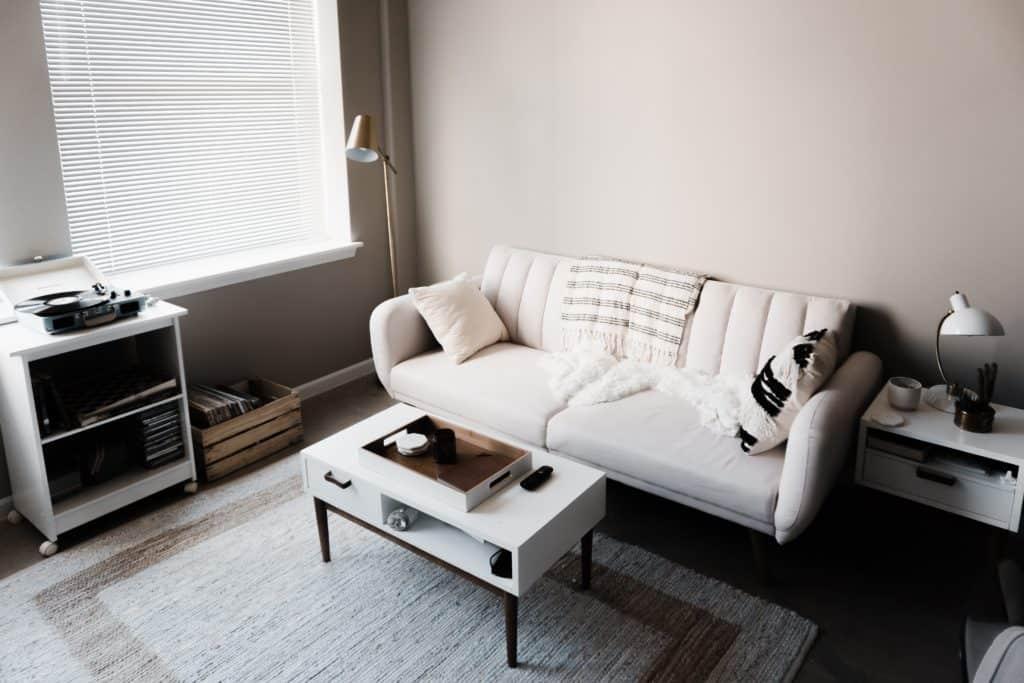 Salón de tonalidades claras de estilo nórdico con sofá en blanco y alfombra beige