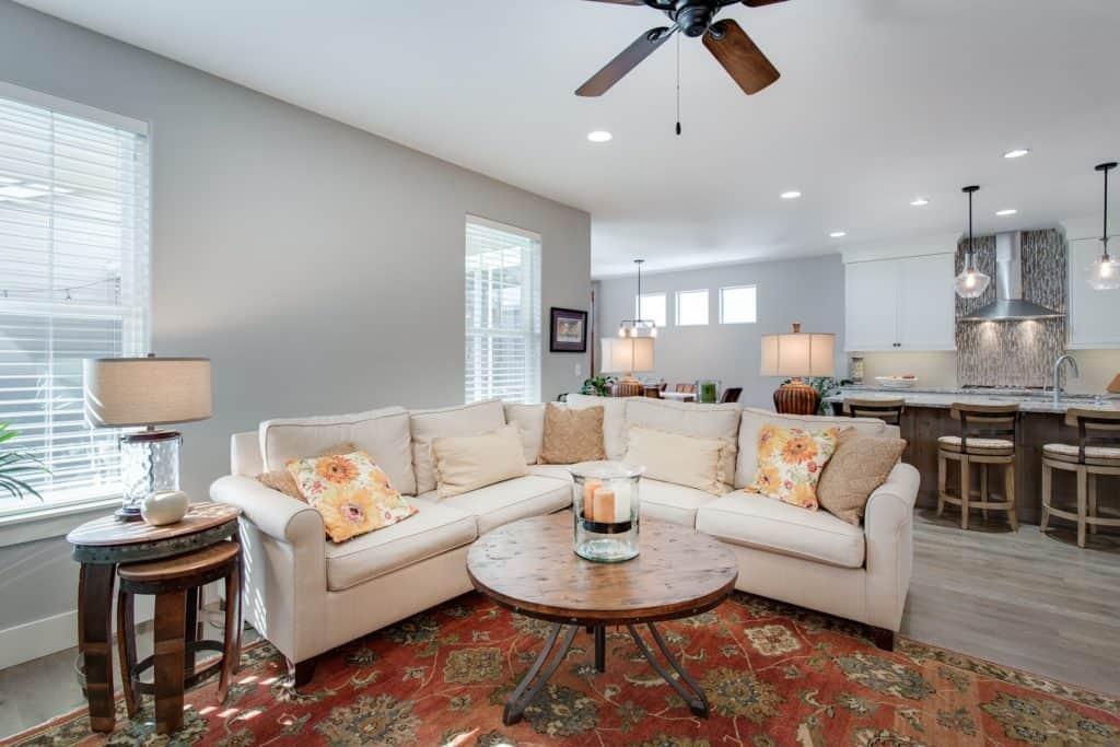 Salón de tonos claros con sofá beige y mobiliario en madera sobre alfombra persa