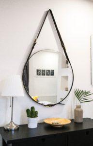 recibidor de madera oscura con pared blanca, espejo y plantas