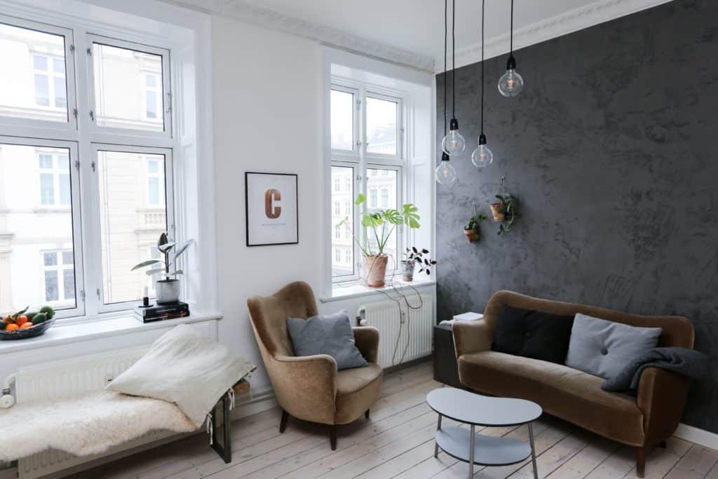 salón decorado modernamente con paredes blancas y una pared en gris oscuro
